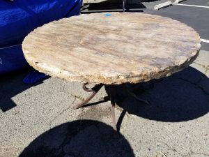 Travertine stone table, round with hammered edge and decorative wrought iron legs